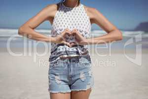 Mid section of woman making heart shape with hands at beach