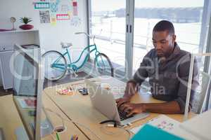 Serious businessman using laptop in creative office