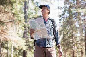 Low angle view of hiker with map standing in forest