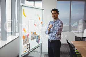 Portrait of smiling executive standing near whiteboard