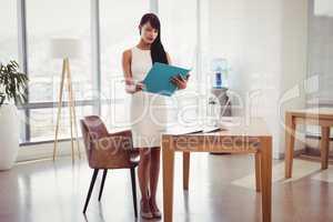 Attentive executive reading file at desk