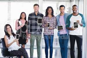 Portrait of creative business team holding tablet pc and mobile phones