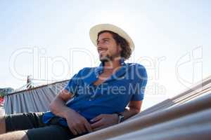 Smiling looking away while relaxing on hammock at beach