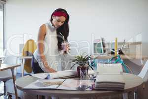 Businesswoman holding drink while working at office desk