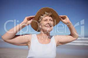 Smiling senior woman wearing sun hat at beach