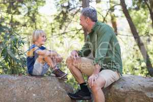 Father and talking while siting on rocks