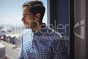 Thoughtful businessman looking through glass window