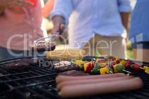 Family grilling patties, vegetables and sausages on the barbecue grill