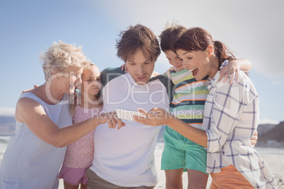 Multi-generation family using mobile phone at beach