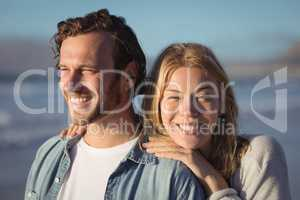 Smiling woman with boyfriend standing at beach