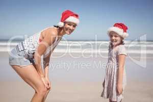 Portrait of happy woman with daughter wearing Santa hat at beach