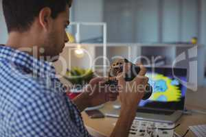 Young graphic designer using camera in office