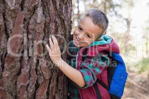 Portrait of happy boy embracing tree