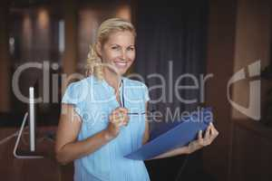 Portrait of smiling executive standing with file