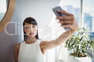 Beautiful executive taking selfie from mobile phone