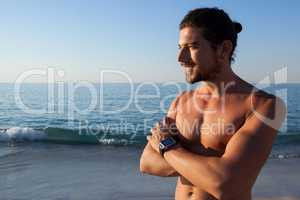 Muscular man standing with arms crossed at beach