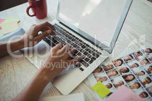 Hands of female photo editor working on laptop in office