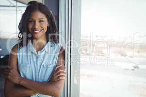 Smiling businesswoman standing by window in office