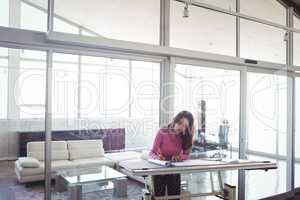 Female interior designer making diagram on paper in office