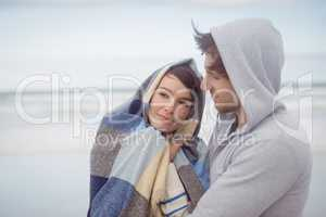 Man embracing her girlfriend wrapped in blanket during winter
