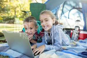 Siblings using laptop outside the tent at campsite