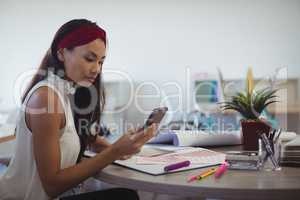 Businesswoman using mobile phone at creative office