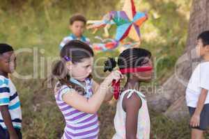 Little girl blindfolding friend at campsite