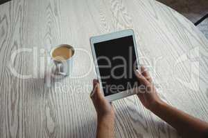 Hands of woman holding holding digital tablet by coffee cup on table
