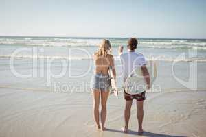 Rear view of couple holding surfboards while standing at beach