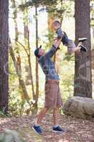 Father lifting son while hiking in forest