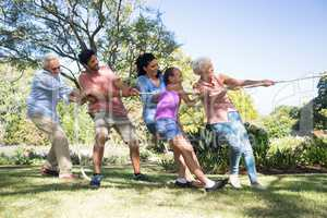Family playing tug of war in the park