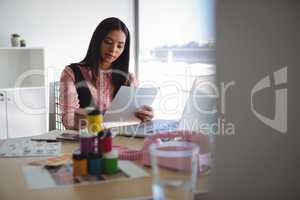 Young businesswoman reading document at creative office