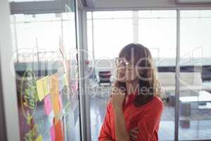 Serious businesswoman looking at adhesive notes in office