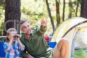 Daughter using binoculars with father in forest