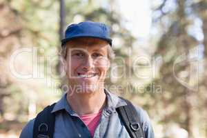 Portrait of happy hiker wearing blue cap