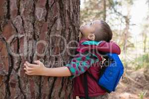 Side view of boy embracing tree