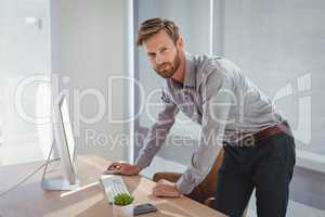 Portrait of confident executive working on personal computer at desk