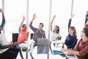 Happy business people with arms raised