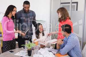 Smiling business people discussing at desk