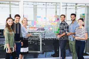 Portrait of business people standing by glass wall