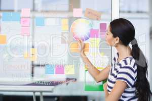 Businesswoman looking at plan on wall