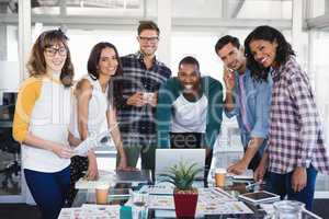 Portrait of creative business team standing around table