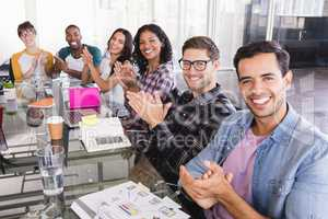 Portrait of business team clapping while sitting at creative office