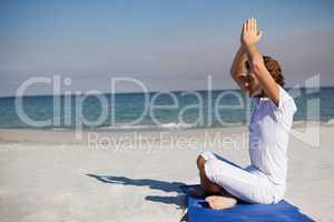 Side view of man meditating at beach
