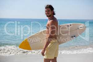 Smiling surfer with surfboard standing at beach coast
