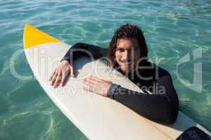 Surfer leaning on surfboard in sea