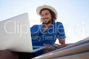 Smiling man using laptop while relaxing on hammock at beach