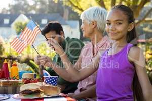 Girl holding american flag near the picnic table