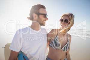 Happy young couple wearing sunglasses at beach