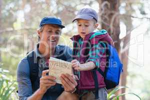 Man and boy reading map in forest